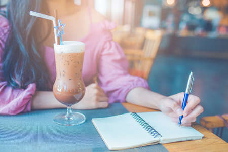 Woman hand is writing on a notebook with a pen.On the table there is a cold cocoa Stock Photo