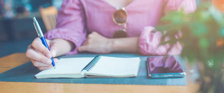 Woman hand is writing on a notepad with a pen.Web banner. Stock Photo