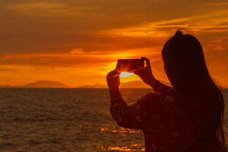 The silhouette of a girl shooting a sunset at the beach. Stock Photo - 122844795