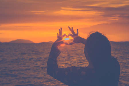 Silhouette woman hand is making a heart-shaped symbol at sunset at the beach. Stock Photo - 122844797