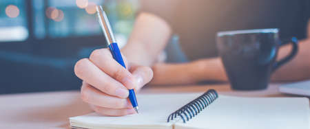 Woman hand is writing on a notepad with a pen in office.Web banner. Stock Photo - 122844803