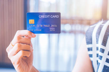 Business woman hand holds a blue credit card. Stock Photo