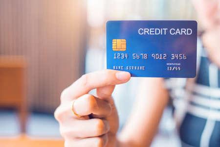 La main de femme d'affaires tient une carte de crédit bleue.