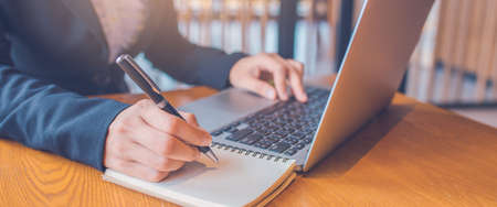 Business women hand are taking notes on paper with a black pen, and she is using a laptop computer on a wooden desk in the office.Web banner.