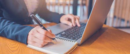 La main des femmes d'affaires prend des notes sur papier avec un stylo noir, et elle utilise un ordinateur portable sur un bureau en bois dans le bureau. Bannière Web.