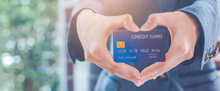 Woman hand are holding a credit card and making a heart-shaped hand.Web banner. Imagens