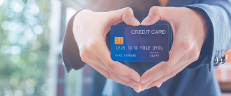 Female businessmen are holding a credit card and making a heart-shaped hand.Web banner.