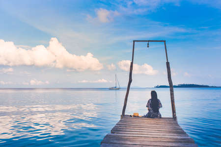 The sea and the clear sky. A day with a female tourist sitting on a wooden bridge.,she looks out at the sea where the boat is sailing.