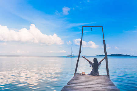 The sea and the clear sky. A day with a female tourist sitting on a wooden bridge.She looked at us on the sail and lifted her hand happily.