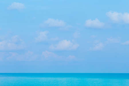 Floating clouds, fluffy colors against the blue sky and the sea
