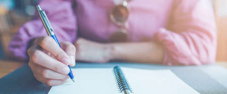 Woman hand taking notes on a notebook using a pen.Web banner. Stok Fotoğraf