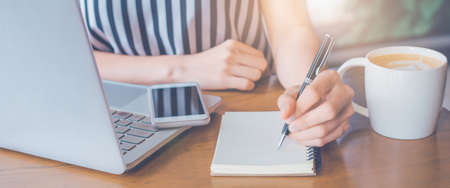 business woman working at a computer and writing on a notepad with a pen.Web banner.