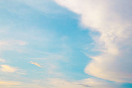 Floating clouds, fluffy colors against the blue sky.