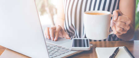 Business woman working at a laptop computer and her hand holding a cup of coffee.Web banner.