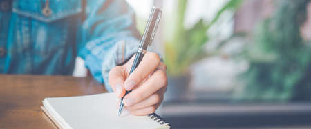 Woman hand is writing on notepad with a pen in the office.Web banner.