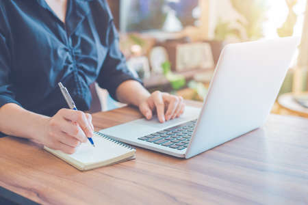 Business woman is writing on a notebook with a pen and using a laptop to work in the office.
