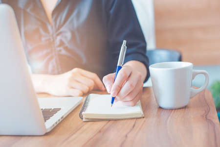 Business woman is writing on a notebook with a pen and using a laptop to work in the office.On a wooden table with a cup of coffee