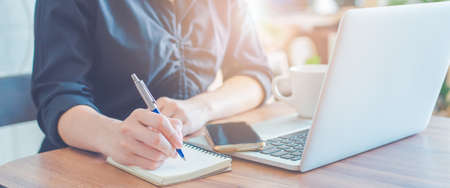 Woman is writing on a notebook with a pen and using a laptop to work in the office.Web banner.