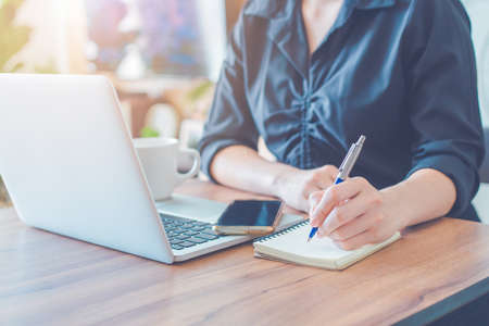 Business woman is writing on a notebook with a pen and using a laptop to work in the office.On the table there is a cup of coffee and a smartphone. Stok Fotoğraf
