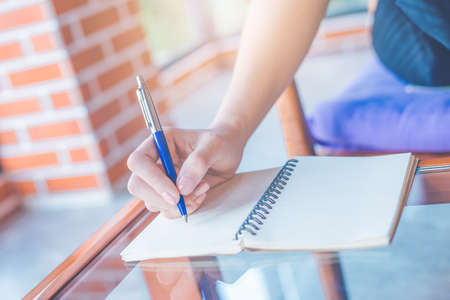 Woman is writing on a notebook with a pen in the office.