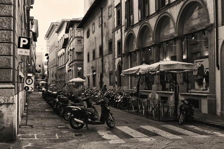 Photo shows the street on which conveniently housed cooperate for scooters and shops  Photo taken in Florence, Italy