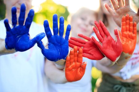 Hands of family members in paint. Playing with paints outdoors.