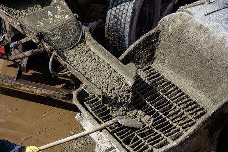 Pouring concrete on a construction site. Concrete is fed from the concrete mixer to the concrete pump Фото со стока