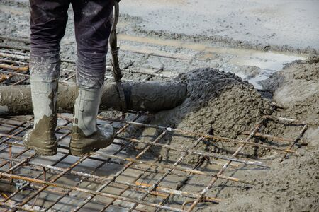 Pouring concrete on a construction site. Concrete is fed from the concrete mixer to the concrete pump, and the worker controls the flow on his floor