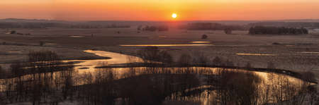 Panorama of sunrise on the river in early spring