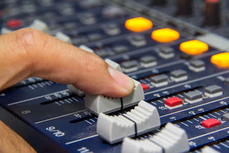 An expert adjusting audio mixing console.select focus photo