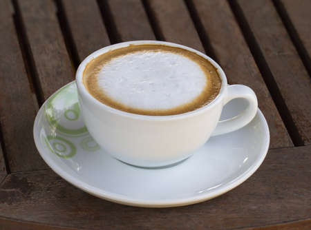 Coffee cup resting on a wooden table.