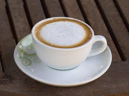 filiżanka kawy: Filiżanka kawy odpoczynku na drewnianym stole.