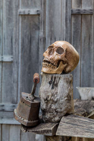 Human skull and Old Iron rests on the old wood. photo