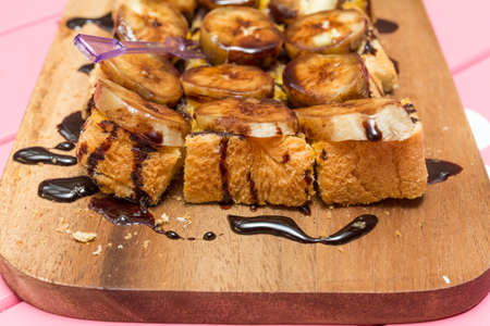 choc: Page toast topped with banana, chocolate Choc was placed on a wooden table Pink. Stock Photo