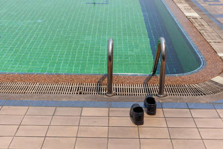beside: Shoes lying beside the pool