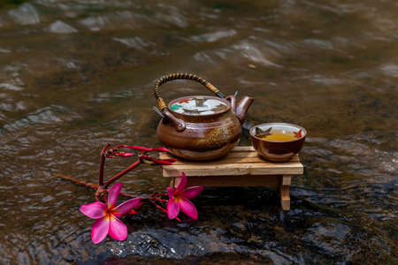 Cup of tea placed on a wooden table in a small stream of water from a waterfall Stock Photo