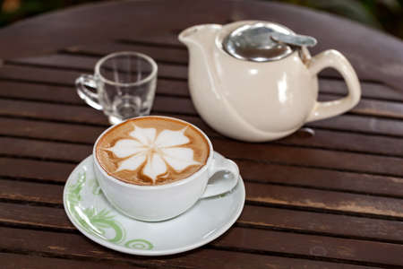 Fresh coffee in the cup. Fresh coffee, flowers and appetizing
