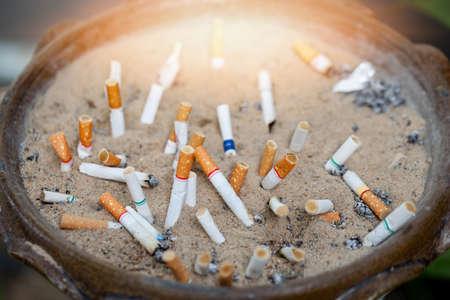 Die Zigarettenkippen werden weggeworfen. Zigaretten sind die Ursache für Mundkrebs. Rauchen ist eine Ursache von Krebs.
