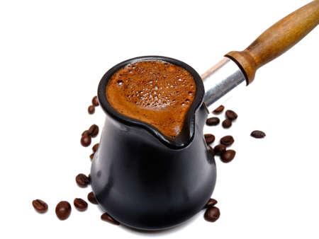 granos de cafe: Café en un turco con fondo de granos de café