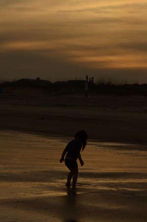 tybee island: girl silhouette against beach sunset