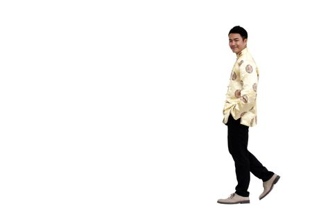 Asian man wear Chinese traditional suit to celebrate chinese new year isolated on white background.  He is walking on the street with smiling face.