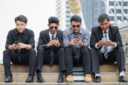 彼らのスマート フォンに着目したビジネスマンのグループ。ニュース、メール、株価指数、自分の仕事をチェックしている彼ら。