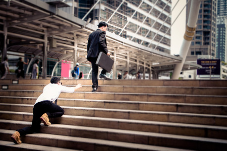 he: Smart Businessman is walking on the steps and heading to his goal. Competition between big and small business. He is carrying the suitcase and keep calm and focus to his mission. Another competitor try to climb on the step to and cannot follow up him