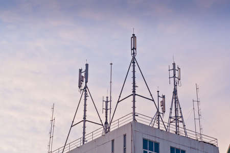 atop: Phone antenna mounted atop a building. Stock Photo