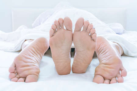 Couples feet sticking out from under DUVET or BLANKET make love at home on bedroom