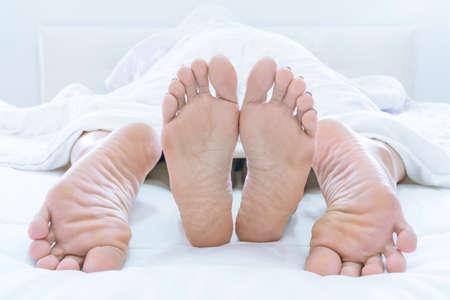 Paarfüße, die unter DUVET oder BLANKET hervorstehen, lieben sich zu Hause im Schlafzimmer