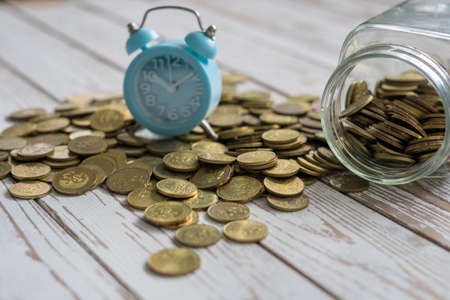 jar of coins with analog alarm clock on vintage wooden table.Financial and investment concept. Banco de Imagens