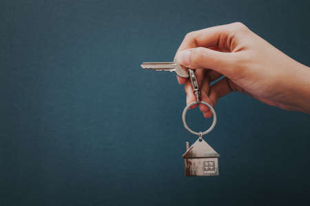 Womans hand holding a house key with House Shape Keychain on green background.