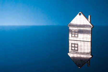 Metal house shape keychain on blue background.