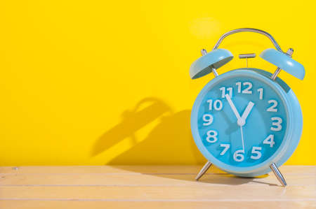 Blue analog alarm clock showing 12 o'clock on yellow background. Archivio Fotografico